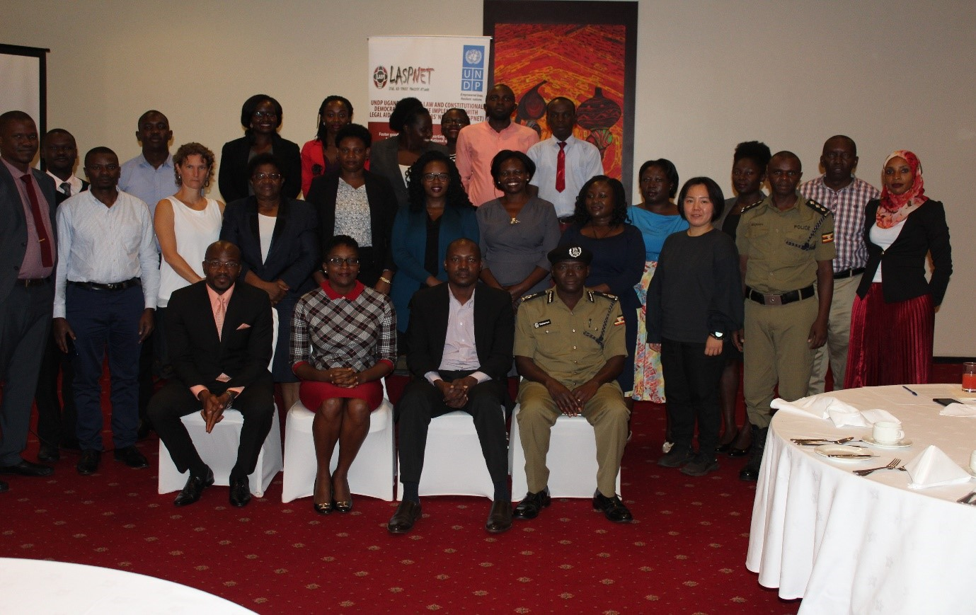 A group photo of the participants; seated extreme left is Mr. Ramsey Bryant (UNHCR); Ms. Sandra Oryema (LASPNET Board Chairperson); Associate Prof. Christopher Mbazira (Lead Consultant) and ACP Anatoli Muleterwa (Uganda Police Force).
